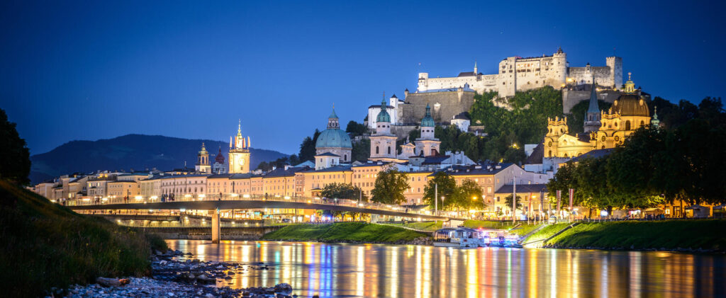 Salzach with the historical old city center and the fortress Hohensalzburg during night